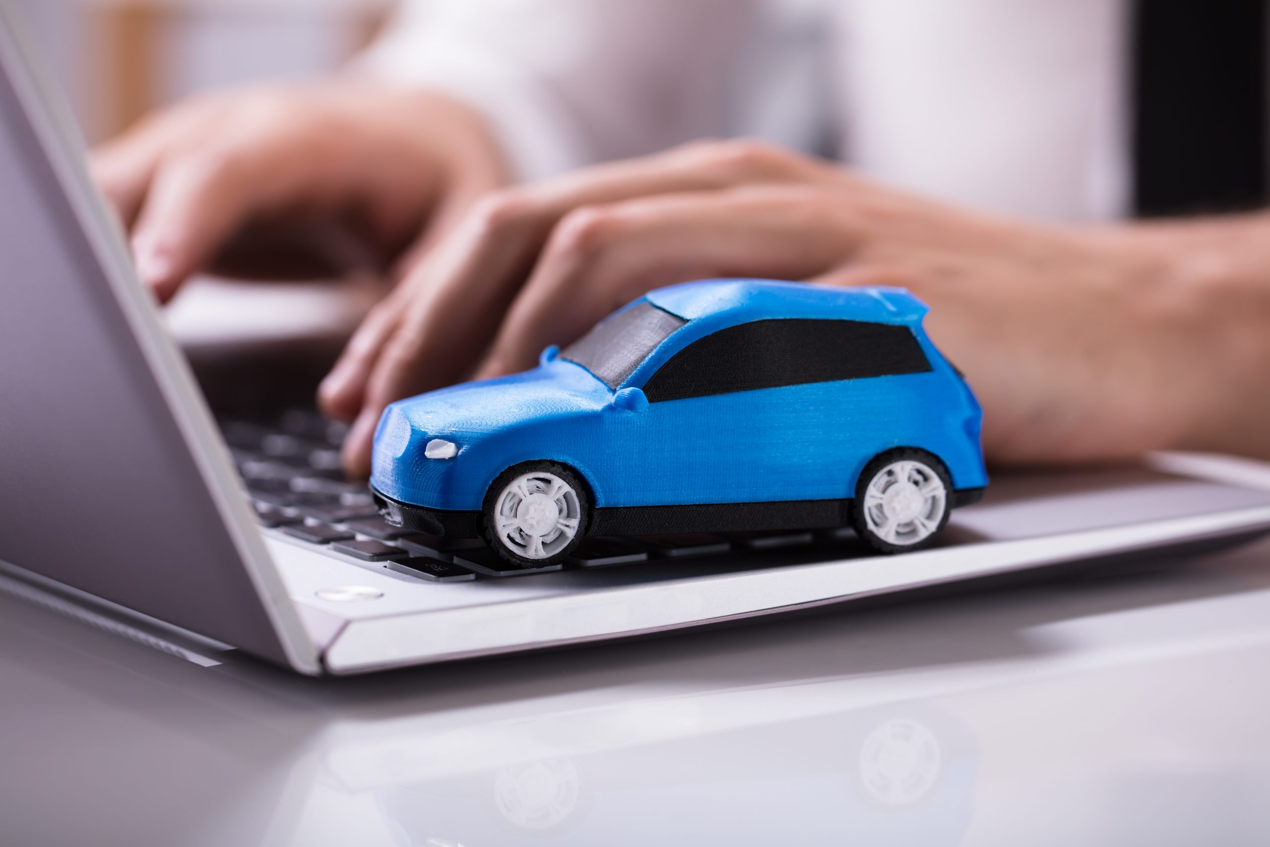 Close-up,Of,A,Small,Blue,Car,On,Laptop,Keypad